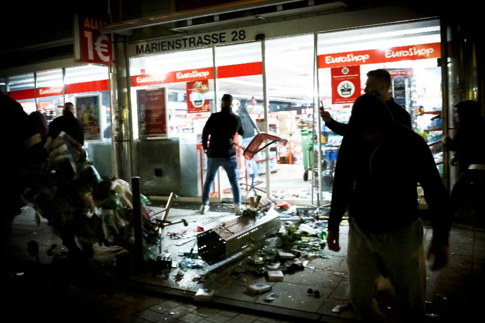 Menschen stehen vor einem geplünderten Geschäft in der Marienstraße in Stuttgart. Bei Auseinandersetzungen mit der Polizei haben dutzende gewalttätige Kleingruppen im Juni die Innenstadt verwüstet und mehrere Beamte verletzt.