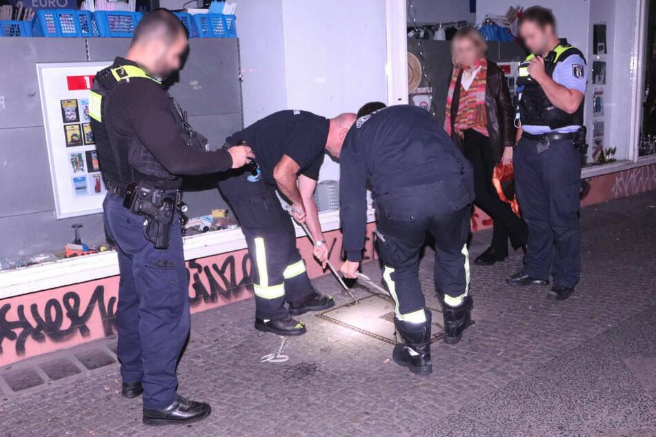 Eine junge Frau (2 .v.r.) hat ihr gestohlenes Handy in der Nacht zu Donnerstag unter einem Schachtdeckel in Berlin-Neukölln geortet und die Polizei informiert.