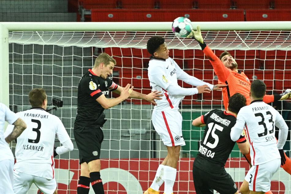 Torhüter Kevin Trapp von Eintracht Frankfurt (M) pariert gegen Lucas Silva Melo von Bayer Leverkusen (M. links).
