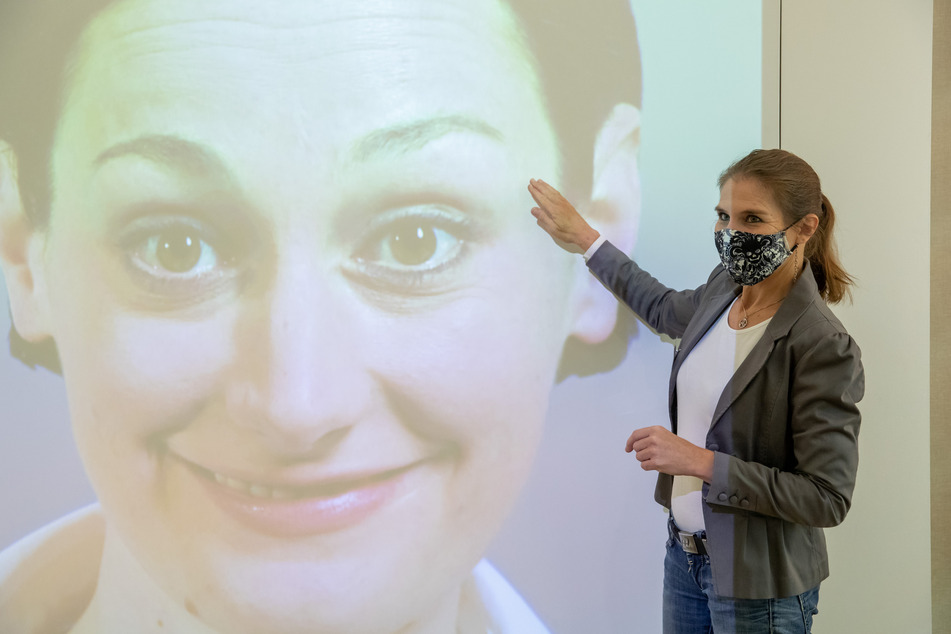 Luna Mittig erläutert Details zur Mimik und Gestik an einer Videoinstallation im Museum für Kommunikation.