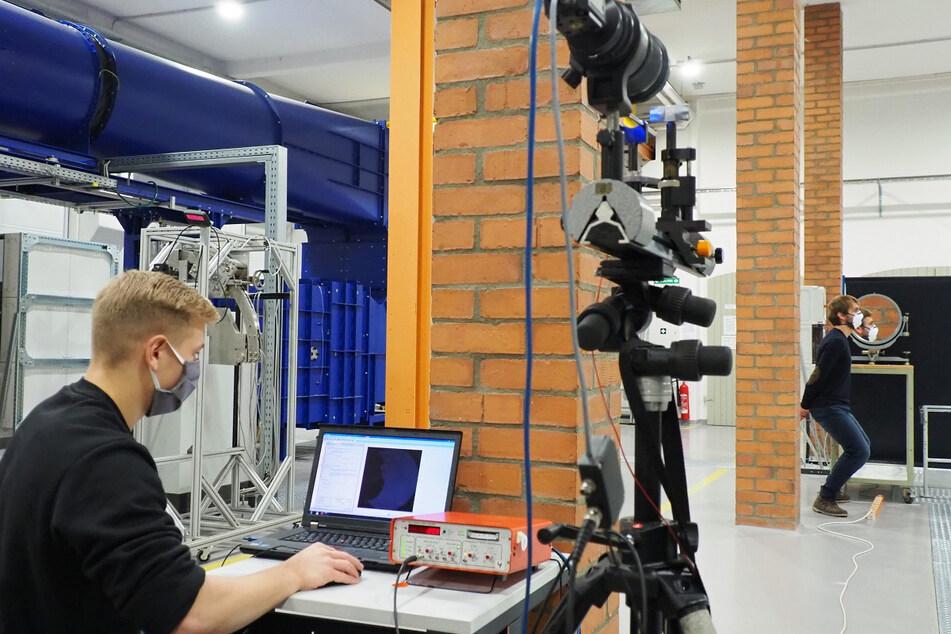 Moritz Kluwe (l.) und Emanuel Thom von der TU Freiberg nehmen das Maskentest-Video in der Versuchshalle der Professur für Strömungsmechanik auf.