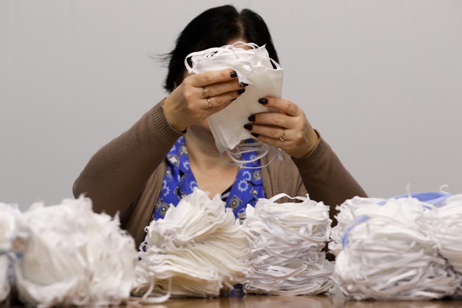 """Eine Mitarbeiterin der staatlichen Fabrik """"Blakit»""""verpackt Mundschutzmasken. (Archivbild)"""