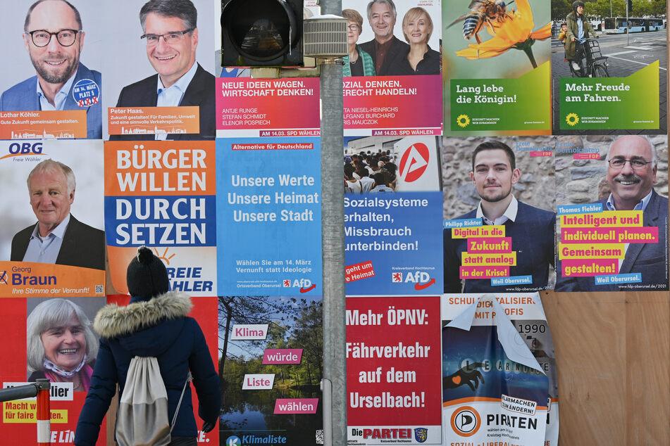 Mit Wahlplakaten werben verschiedene Parteien an einer Plakatwand in Oberursel um die Stimmen bei der Kommunalwahl.