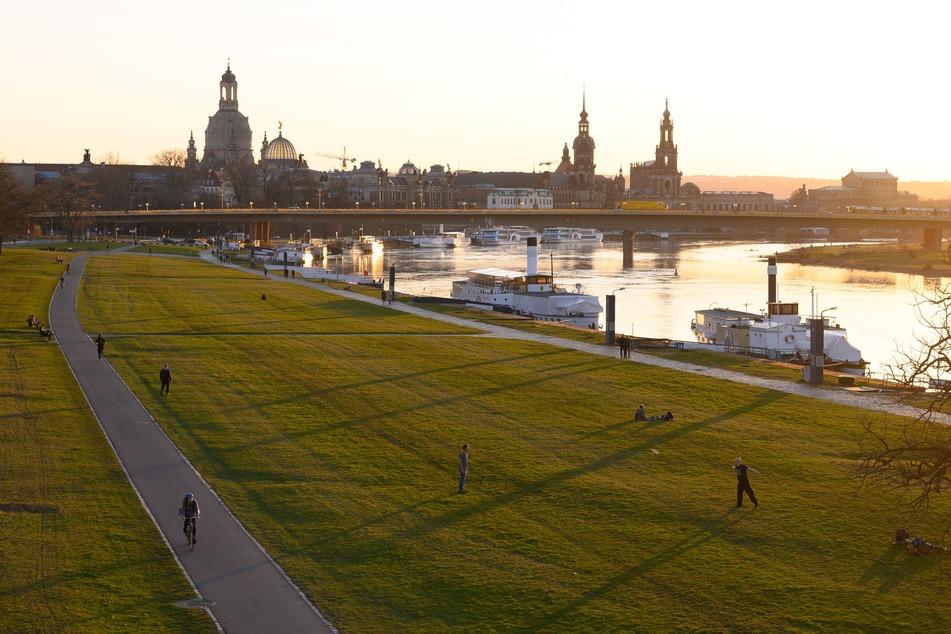 Menschen verbringen ihre Zeit am Ufer der Elbe vor der Kulisse der Altstadt.