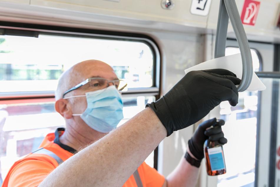 In einem Fahrzeug der Ruhrbahn bestreicht ein Mitarbeiter einen Haltegriff mit einem Spezialmittel.