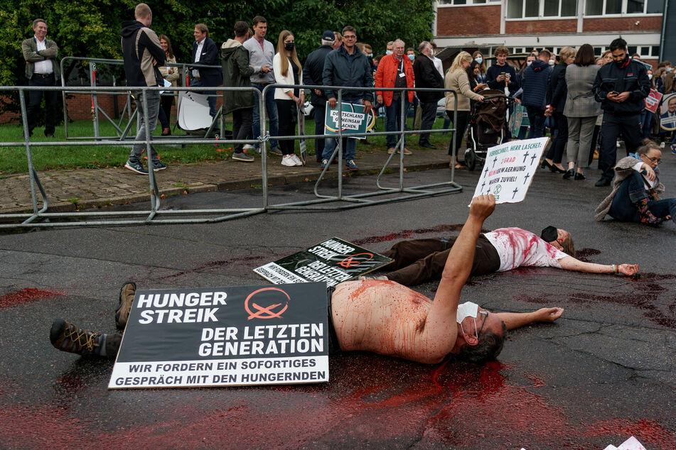 """Klimaaktivisten liegen mit Kunstblut übergossen auf dem Boden. """"Verrechnet Herr Laschet. 2 Grad Klimaerwärmung waren zu viel"""", steht auf einem der Plakate."""