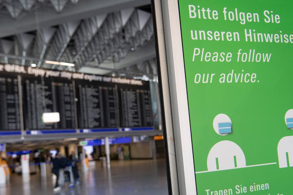 Warnschilder stehen an den Eingangstüren des Terminals am Flughafen Frankfurt.