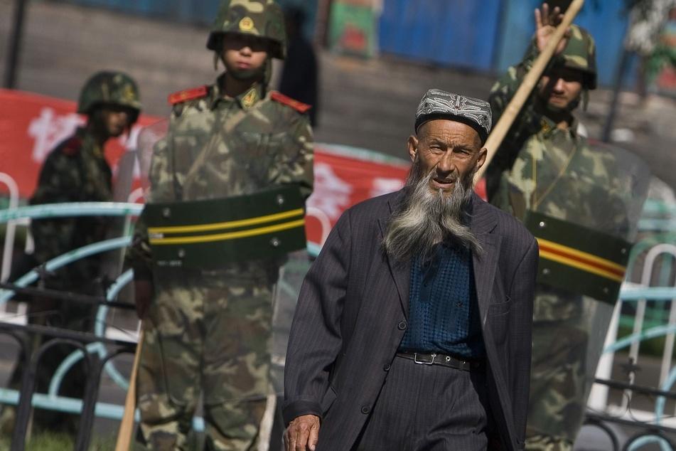 Ein Angehöriger der uigurischen Minderheit in China geht in der Unruheregion Xinjiang in Nordwestchina vorbei an chinesischen Sicherheitskräften.