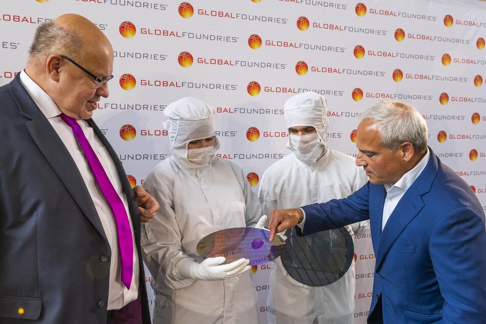 Altmaier (l.) und Caulfield (r.) neben Auszubildenden, die 300-Millimeter-Wafer in der Chipfabrik von Globalfoundries halten.