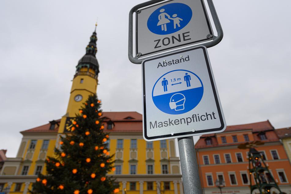 Sachsen, Bautzen: Ein Hinweisschild für die Maskenpflicht und den Abstand ist am Marktplatz vor dem Rathaus, einem Weihnachtsbaum und einer Pyramide zu sehen.