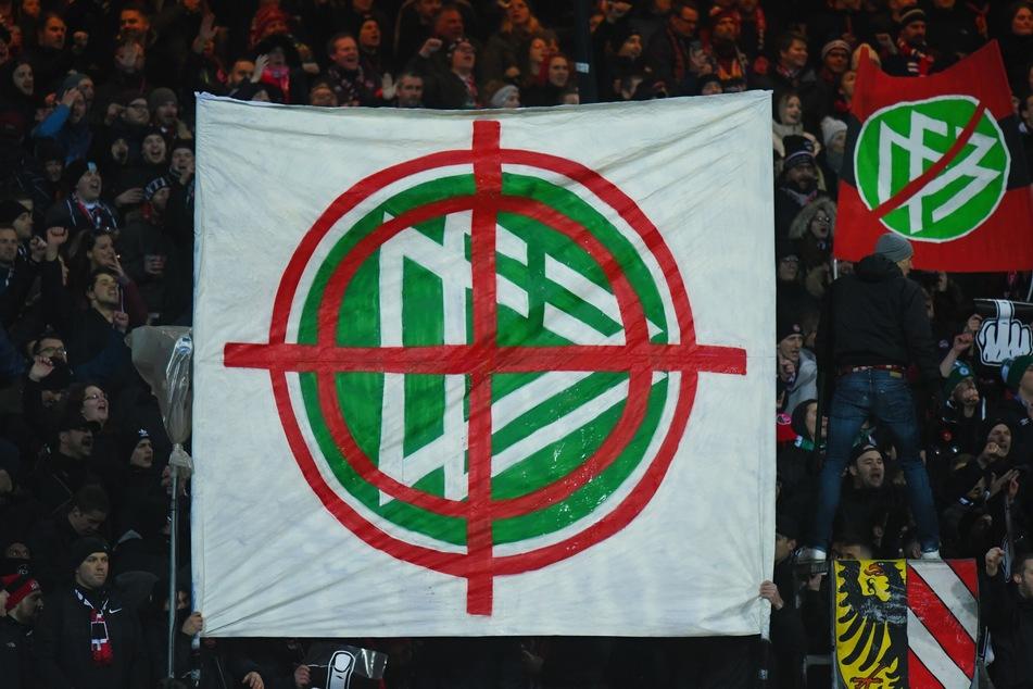 Nürnberger Fans halten ein Banner mit dem Logo des DFB in die Höhe, das in einem Fadenkreuz zu sehen ist.