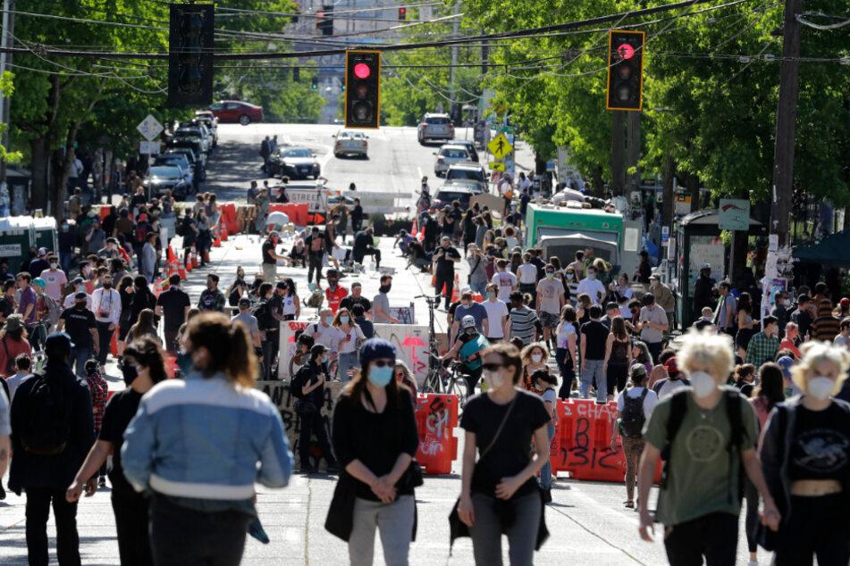 """Seattle: Menschen gehen auf einer Straße in der Nähe des Cal Anderson Parks an Barrikaden vorbei, innerhalb der so genannten """"Capitol Hill Autonomous Zone""""."""