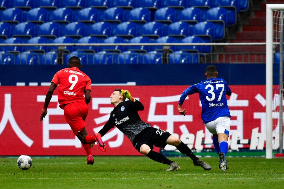 S04-Keeper Markus Schubert (M.) wird in der Nachspielzeit von Augsburgs Sergio Cordova (l.) umkurvt, der danach zum 3:0 für den FCA einschiebt. Münir Mercan hatte den Ball davor als letzter Mann verstolpert.