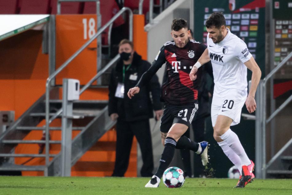 Bayerns Lucas Hernández (l.) im Duell mit Augsburgs Rechtsverteidiger Daniel Caligiuri.