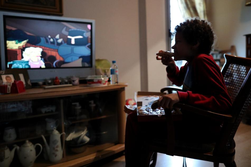 Ein Kind isst ein Stück Pizza, während es zu Hause fernsieht. Das Europa-Büro der Weltgesundheitsorganisation WHO warnt davor, dass die Coronavirus-Pandemie wahrscheinlich zu mehr Fettleibigkeit unter Kindern führen wird.