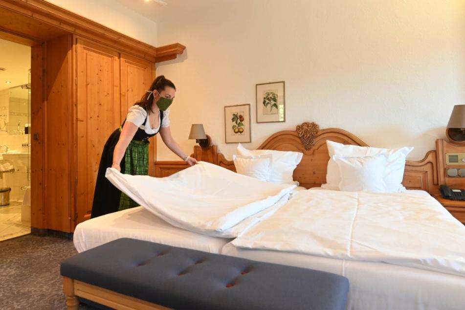 Eine Mitarbeiterin bereitet ein Hotelzimmer vor.