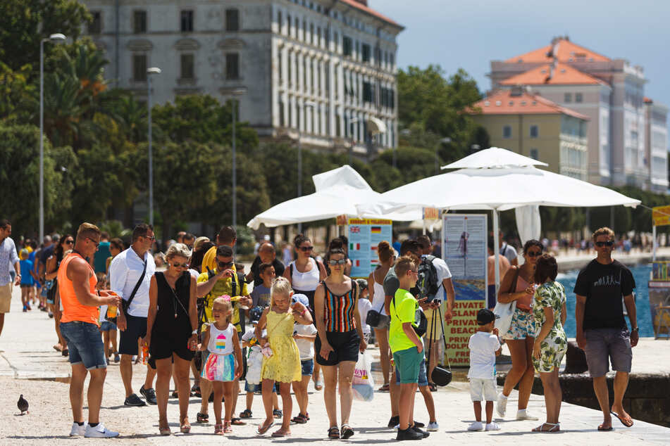 Kroatien, Zadar: Touristen spazieren an der Uferpromenade entlang.
