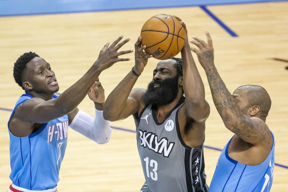 James Harden (M) von den Brooklyn Nets gegen Victor Oladipo (l) und P.J. Tucker (r) von den Houston Rockets.