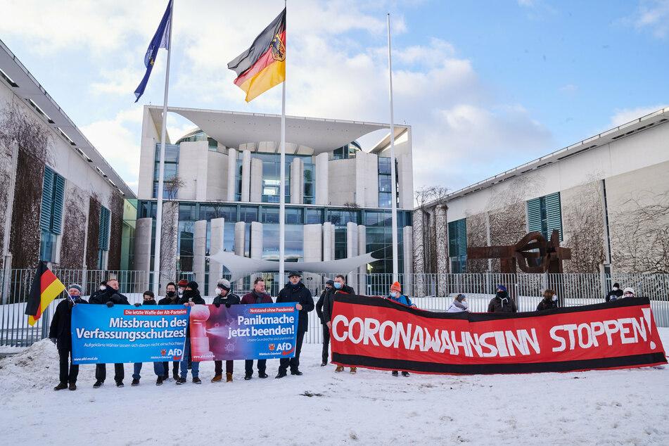 """""""Missbrauch des Verfassungsschutzes"""", """"Panikmache jetzt beenden!"""" und """"Coronawahnsinn stoppen"""" steht auf den Transparenten, die Demonstranten vor dem Kanzleramt halten."""