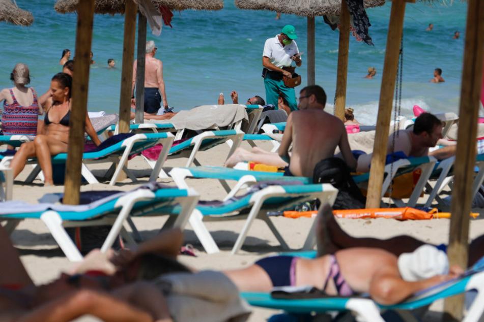 Palma: Menschen sonnen sich und schwimmen am Strand von Arenal auf Mallorca. Angesichts erhöhter Ansteckungsgefahren hat die Bundesregierung fast ganz Spanien einschließlich Mallorca als Risikogebiet eingestuft. Die Einstufung bedeutet, dass für heimkehrende Urlauber eine Testpflicht auf das Coronavirus greift.