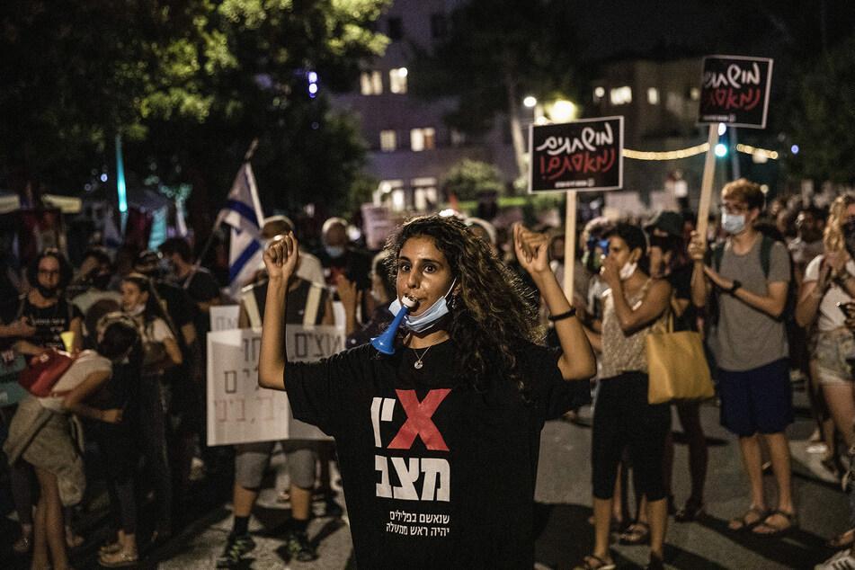 16. Juli, Jerusalem: Eine Frau nimmt an einem Protest gegen den israelischen Ministerpräsidenten Netanjahu in der Nähe seiner Residenz teil. Netanjahu wurde in mehreren Fällen wegen Bestechung, Betrug und Vertrauensbruch angeklagt, streitet aber alle Anklagepunkte ab.