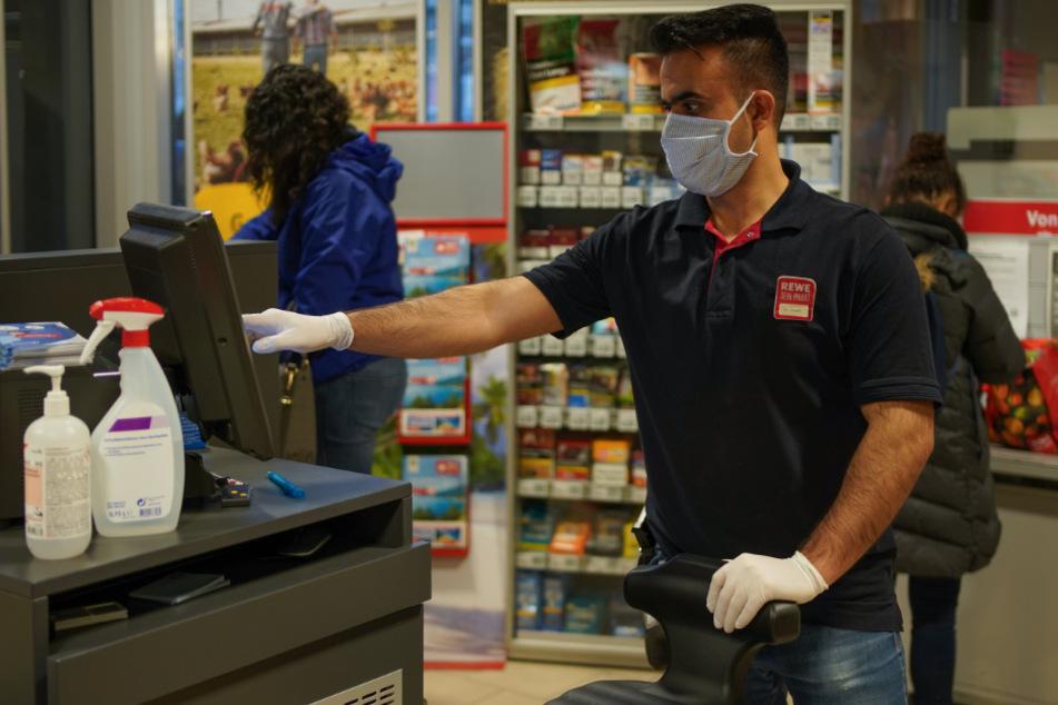 Mundschutz und Handschuhe sieht man bei den Kassierern jetzt immer häufiger.
