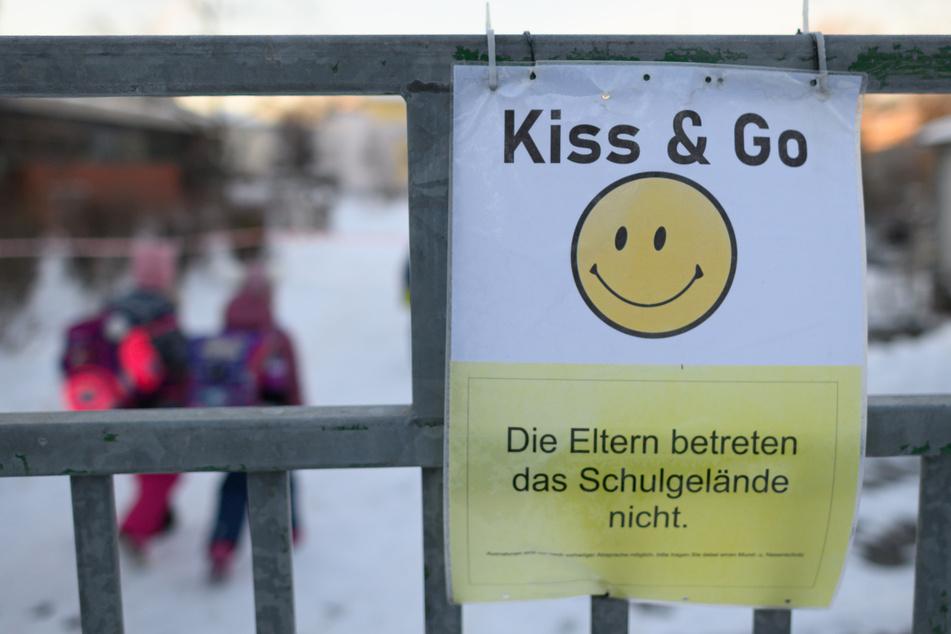 """Das Schild mit einem Smiley und der Aufschrift """"Die Eltern betreten das Schulgelände nicht"""" hängt am Tor der Regenbogenschule in Dresden."""
