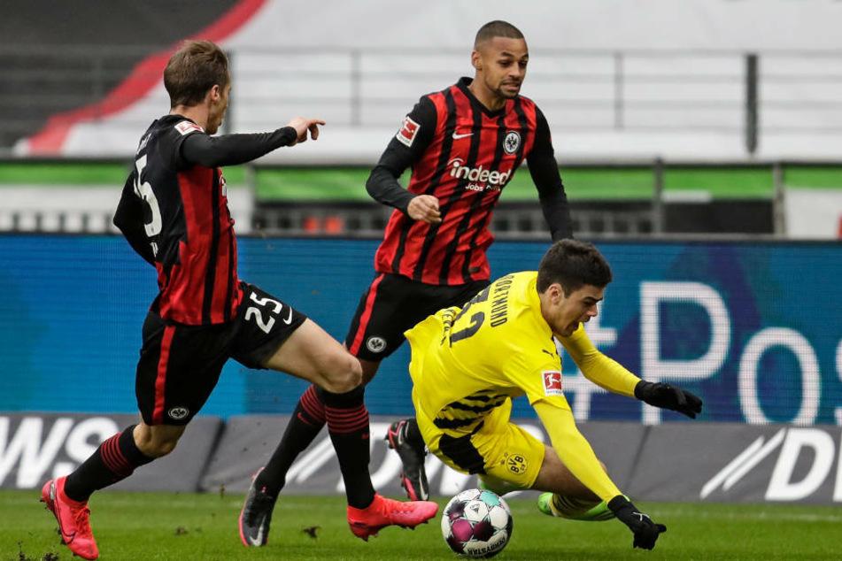 Die Frankfurter Erik Durm (l.) und Djibril Sow (M.) bringen Dortmunds Giovanni Reyna zu Fall.