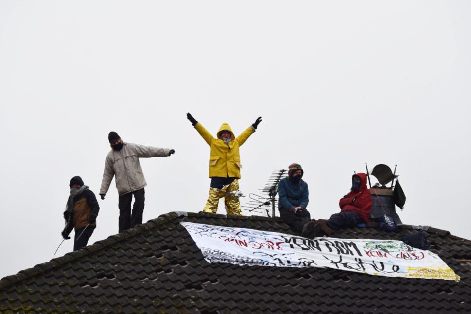 Fünf Aktivisten haben auf dem Dach eines ehemaligen Wohnhauses gegen den Braunkohle-Tagebau demonstriert.