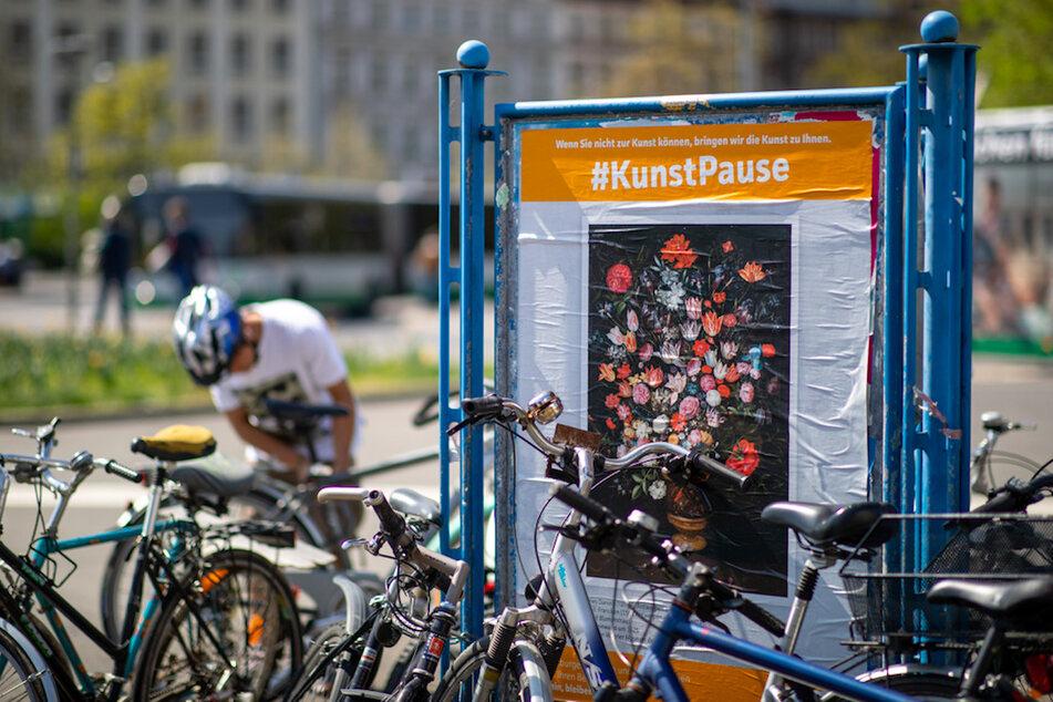 Ein Plakat mit einem Gemälde aus der Sammlung der Würzburger Museen hängt im Rahmen der Aktion #KunstPause auf einem Plakatständer in der Innenstadt.