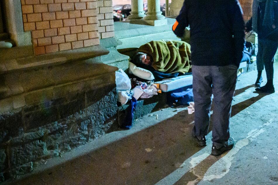 Sozialarbeiter schauen nach einem Mann, der im Durchgang einer Frankfurter Kirche schläft.