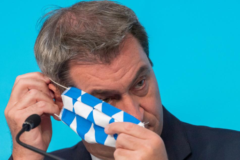 Markus Söder setzt sich nach einer Pressekonferenz zur Corona-Lage in Mamming seine Mundschutzmaske auf.