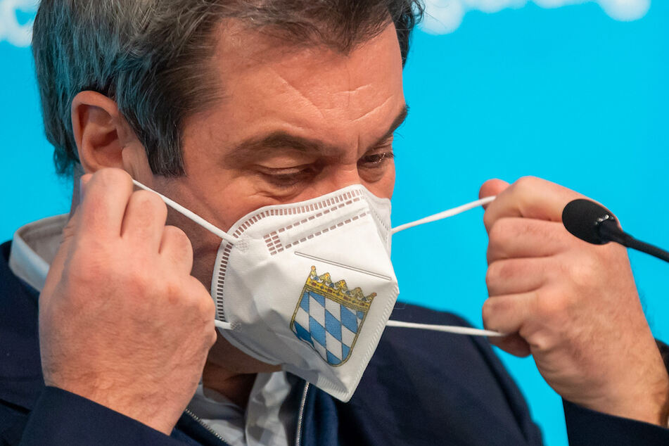 Markus Söder (CSU), Ministerpräsident von Bayern, nimmt sich vor Beginn einer Pressekonferenz eine FFP-2 Maske, die mit dem bayerische Staatswappen auf der Vorderseite bedruckt ist, vom Gesicht ab.