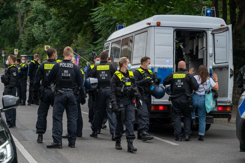 Ein Polizist führt eine Demonstrantin in einen Polizeiwagen, während sich Demonstranten aus Protest gegen die Corona-Politik vor dem Märchenbrunnen in Berlin-Friedrichshain versammeln.