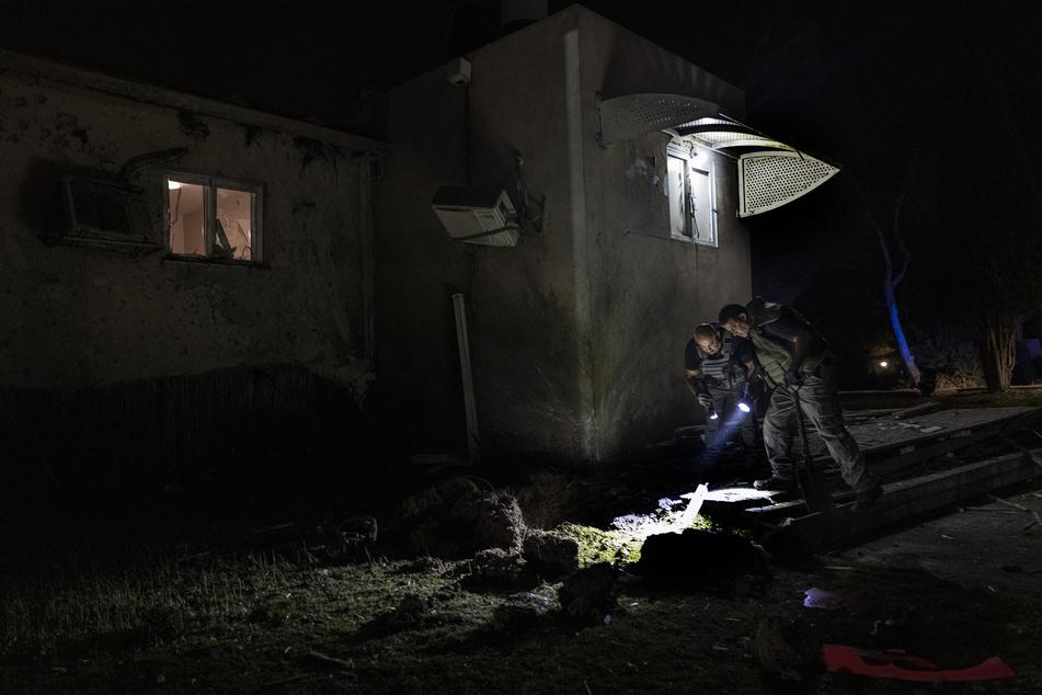 Israelische Polizisten inspizieren den Schaden an einem Haus, das von einem aus dem Gazastreifen abgefeuerten Raketenwerfer getroffen wurde, in einem Kibbuz nahe der Grenze zwischen Israel und dem Gazastreifen.