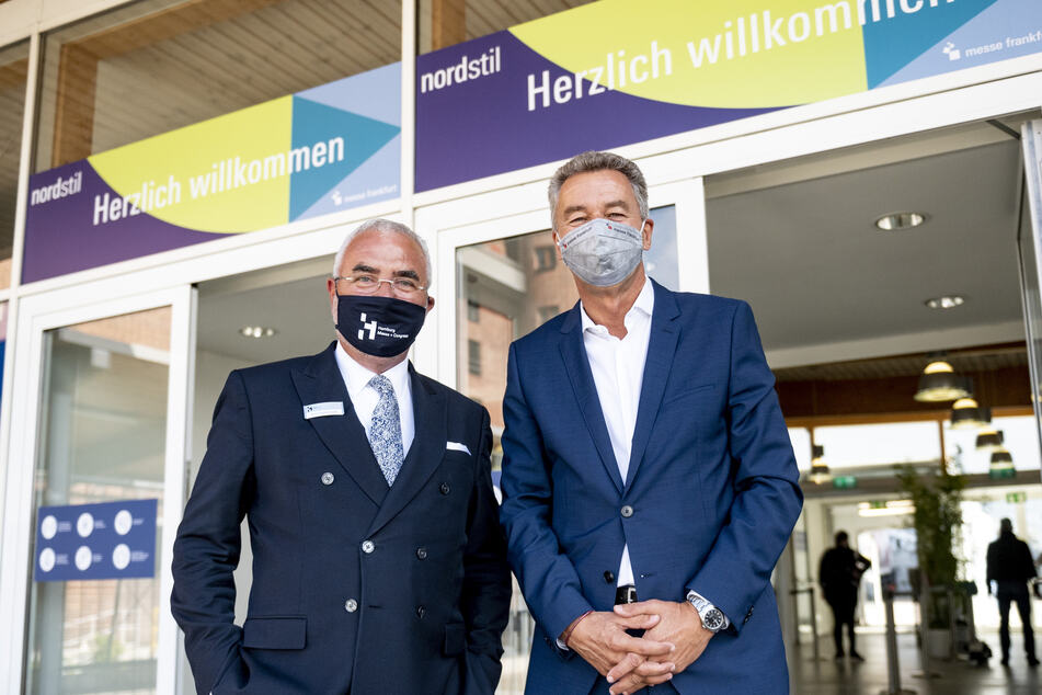"""Detlef Braun (r), Geschäftsführer der Messe Frankfurt, und Bernd Aufderheide, Vorsitzender der Geschäftsführung der Hamburg Messe und Congress (HMC), stehen mit Mundschutz vor dem Eingang der Messehallen bei der Eröffnung der Konsumgütermesse """"Nordstil""""."""