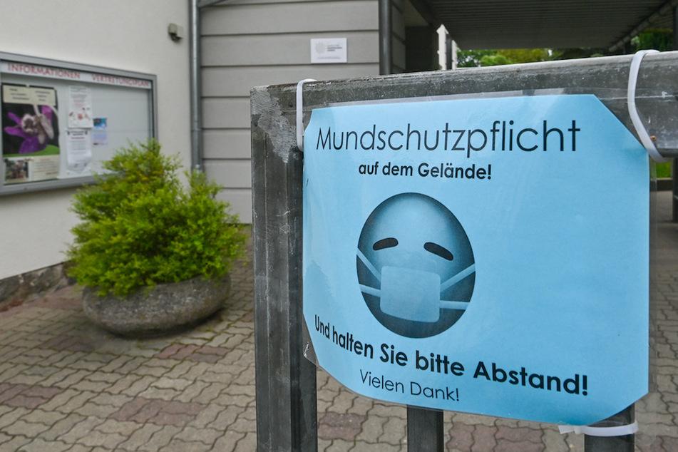 Ein Schild vor einer Schule fordert zum Tragen einer Maske auf.