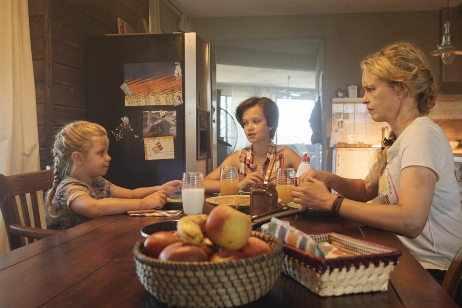 Am Anfang ist noch alles gut: Wiebke (r., Nina Hoss) sitzt mit ihren Adoptivtöchtern Nicolina (Mitte, Adelia-Constance Giovanni Ocleppo) und Raya (Katerina Lipovska) am Küchentisch.