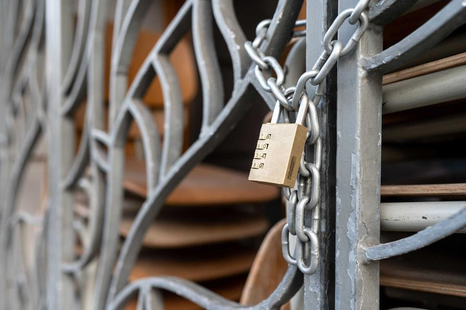 Nordrhein-Westfalen, Köln: Stühle sind hinter dem geschlossenen Gitter eines Restaurants gestapelt.