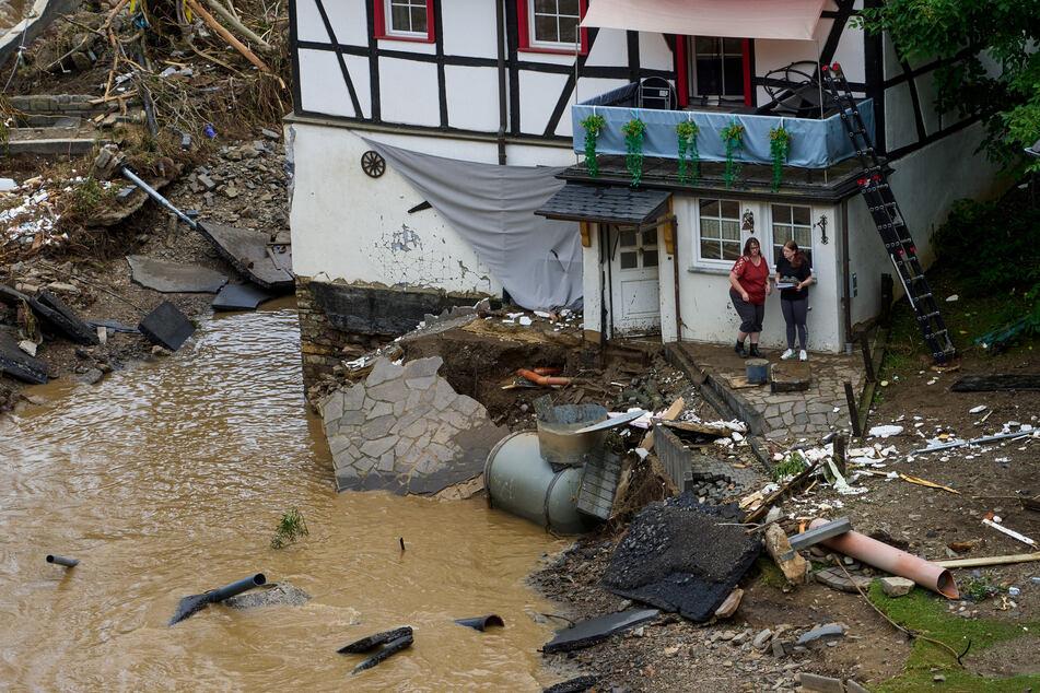 Zwei Frauen stehen neben Trümmern vor einem Haus in dem Ort im Kreis Ahrweiler am Tag nach dem Unwetter mit Hochwasser.