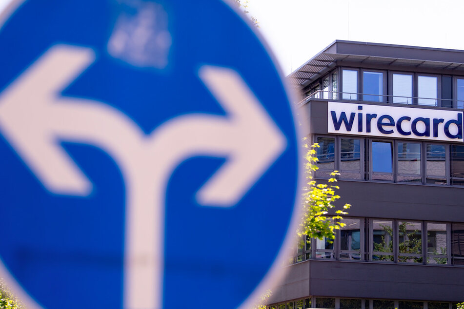 Der Schriftzug von Wirecard ist an der Firmenzentrale des Zahlungsdienstleisters in Aschheim zu sehen. Davor steht ein Verkehrsschild.