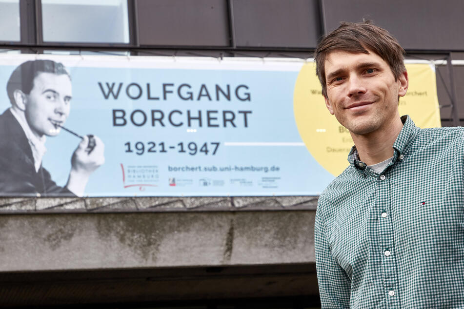 Konstantin Ulmer, Kurator, steht vor der Universitätsbibliothek Hamburg vor einem Banner mit dem Konterfei des Schriftstellers.
