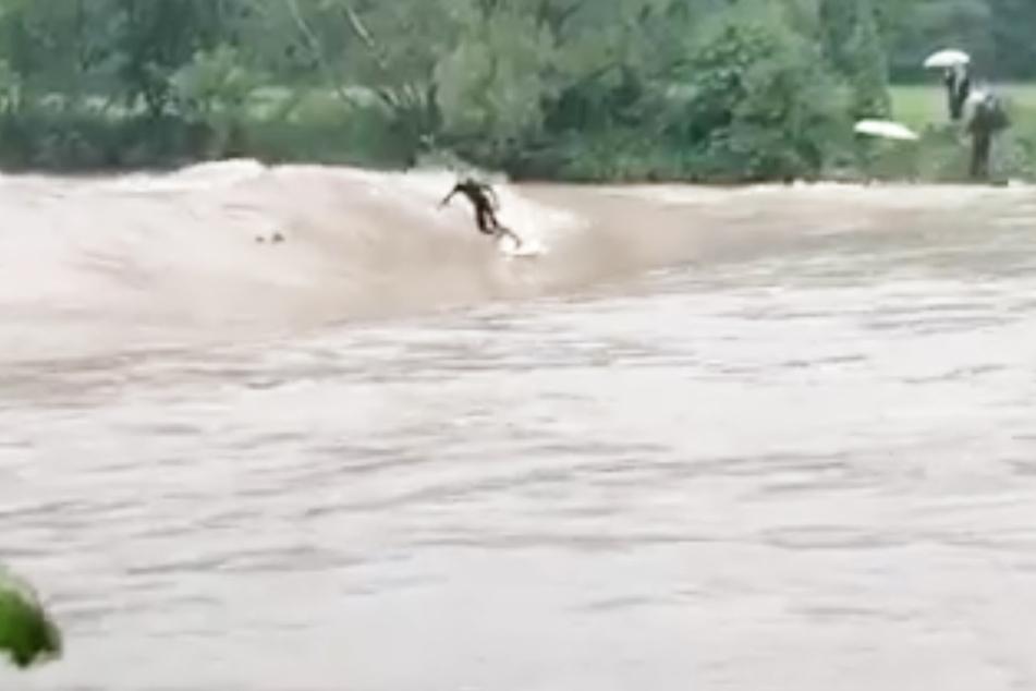Ein Mann surft auf der Welle eines Flusses, drei weitere warten auf ihre Gelegenheit.