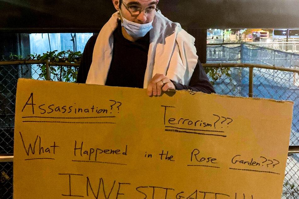 """Will, Anhänger von US-Präsident Donald Trump, steht mit einem Schild mit der Aufschrift """"Assassination?? Terrorism??? What happened in the rose garden??? Investigate!!!"""" (Attentat?? Terrorismus??? Was passierte im Rosengarten??? Ermittelt!!!) gegenüber dem Eingang zum Walter-Reed-Militärkrankenhaus."""