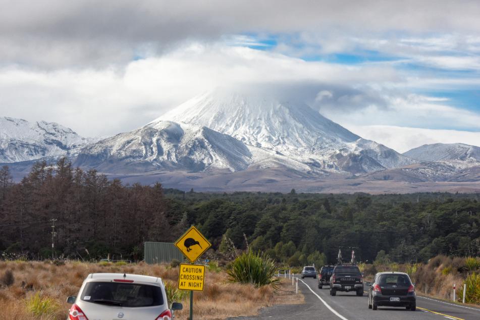 Autos sind auf dem Weg zum schneebedeckten Vulkan Ngauruhoe, einem der Ski-Gebiete des Landes. Wie in vielen anderen Ländern leidet die neuseeländische Tourismusbranche stark unter der Corona-Krise.