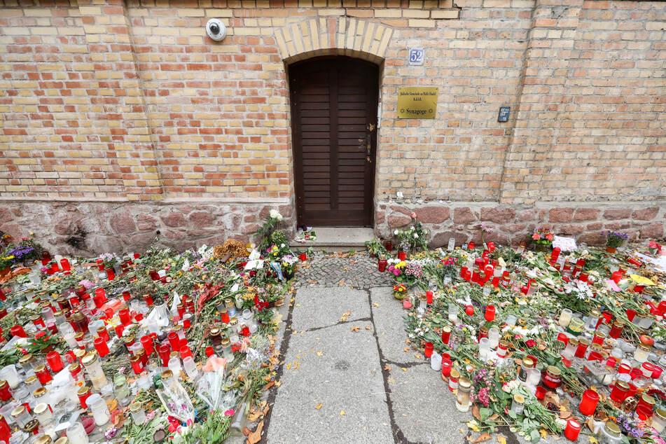 Blumen und Kerzen liegen nach dem Anschlag vor der Tür der Synagoge on Halle.