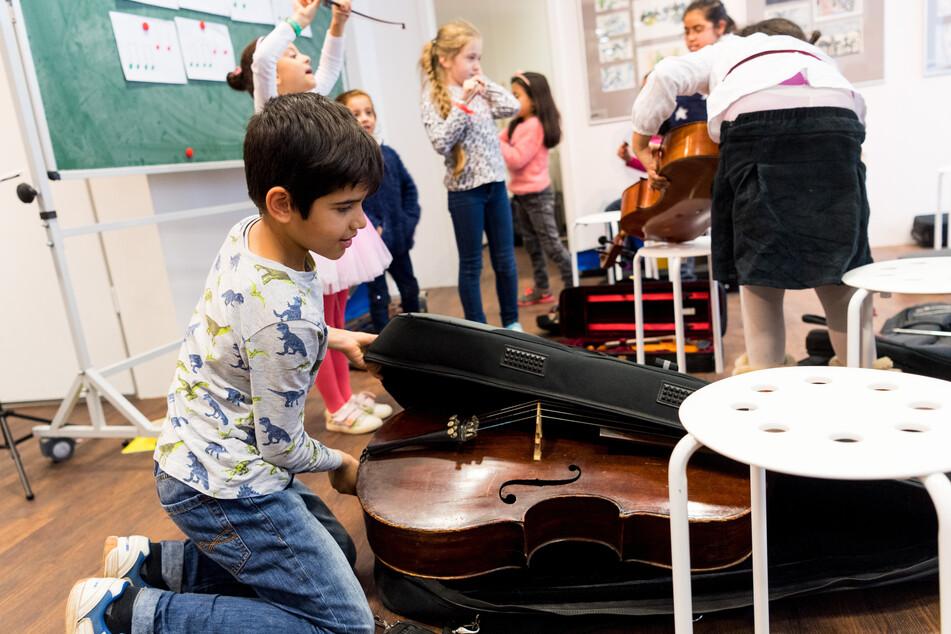 """Ali (9) packt nach dem Musikunterricht des Projekts """"Musaik"""" in Dresden-Prohlis sein Cello ein."""