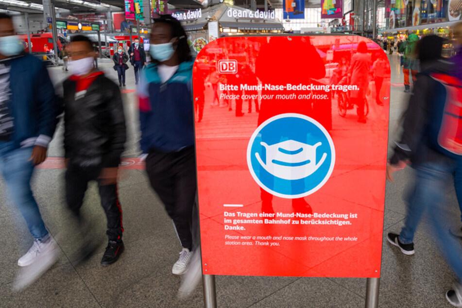"""""""Bitte Mund-Nase-Bedeckung tragen"""" steht in deutscher und englischer Sprache auf einem roten Schild im Eingangsbereich des Münchner Hauptbahnhofs."""