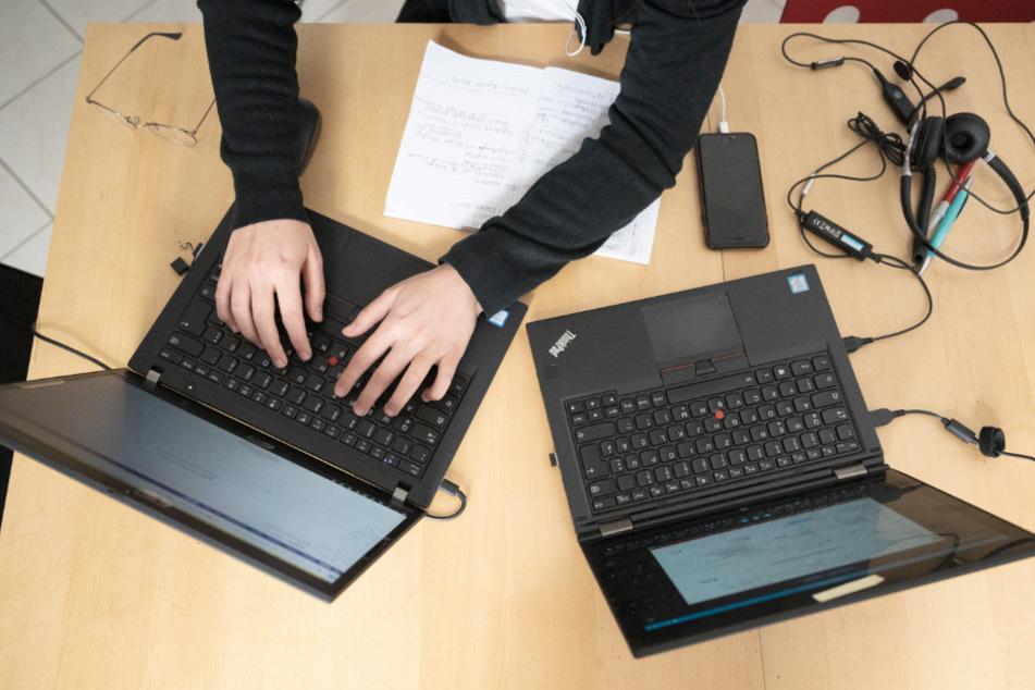 Eine Frau arbeitet im Homeoffice an ihren Laptops.