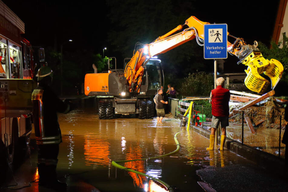 Feuerwehr und Helfer mit schwerem Gerät beseitigen Schäden nach schweren Unwettern in Ettenbeuren.